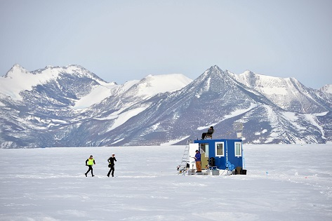 Corredores del Antarctic Ice Marathon cruzando frente a un contenedor de la base polar Union Glacier Camp_© Mike King
