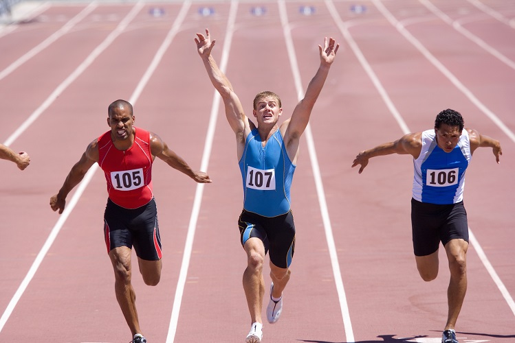 Male sprinters on track, man with arms raised, elevated view