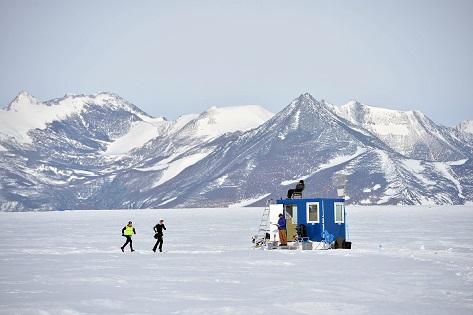 Corredores del Antarctic Ice Marathon cruzando frente a un contenedor de la base polar Union Glacier Camp_© Mike King